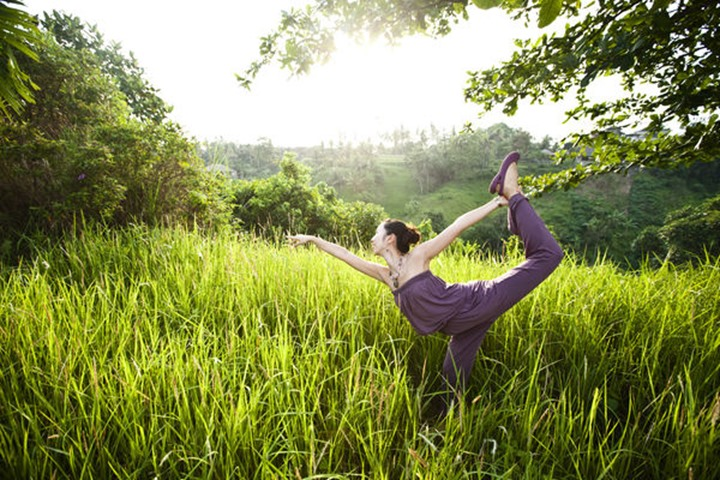 A athletic woman practing yoga in a lush field in Ubud, Bali, Indonesia.