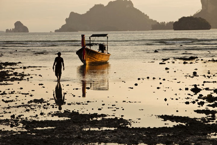 A man walking away from his longtail boat at sunset in Railay, Thailand.