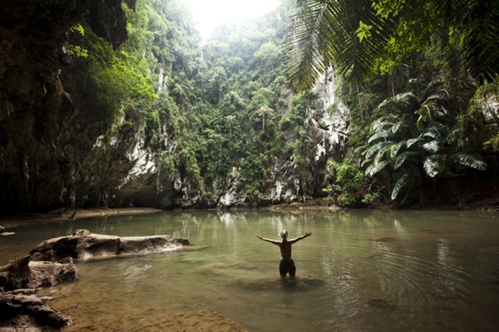 A beautiful young woman adventuring deep into a remote jungle pool relaxes in Tonsai, Thailand.