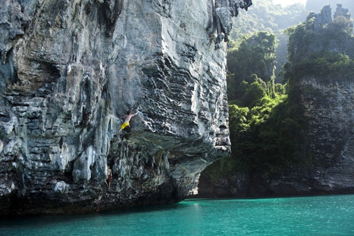 Two athletic men deep water soloing, rock climbing with out ropes near Railay, Thailand.