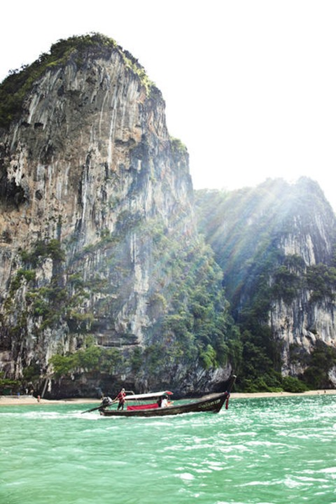 A longtail boat transporting a group of people next to huge limestone cliffs and turquoise water to Railay Beach, Thailand.