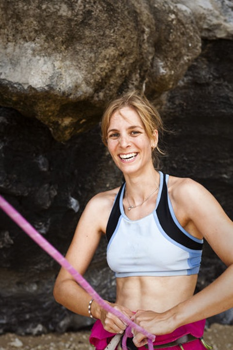 A athletic women rock climber smiling at the camera in Railay, Thailand.