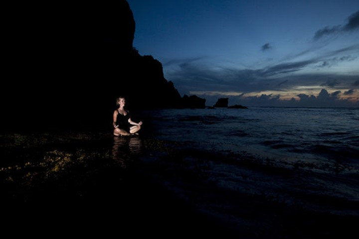 A young woman meditating at sunset next to the ocean in Uluwatu, Bali Indonesia.