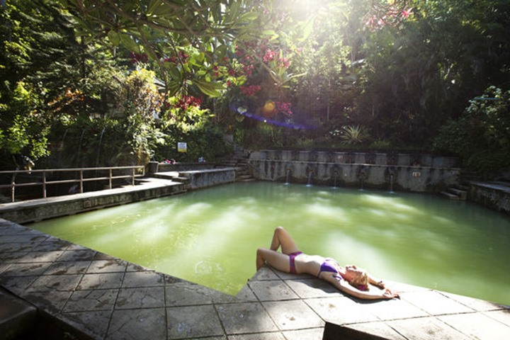 A beautiful woman relaxing next to a hot springs surrounded by a lush jungle and flowers in Lovina, Bali, Indonesia.