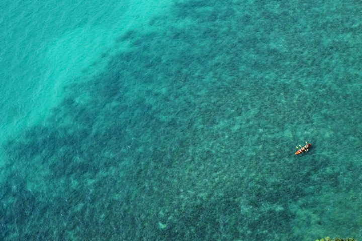 A aerial view of a couple kayaking in turquoise water near Railay, Thailand.