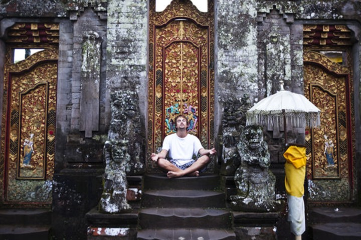 A man sitting on the steps of the Ulun Dabu Beratan Temple meditates with a foggy background in Bali, Indonesia.