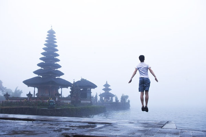 A man leaping into the air on the steps of the Ulun Dabu Beratan Temple with a foggy background in Bali, Indonesia.