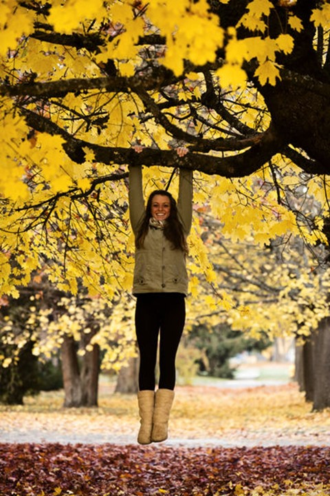 A beautiful young woman smiles while hanging from a tree in the peak fall colors in the Sandpoint, Idaho.