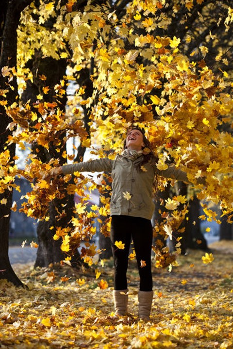 A beautiful young woman smiling throws orange leaves into the air surrounded by fall colors in Sandpoint, Idaho.