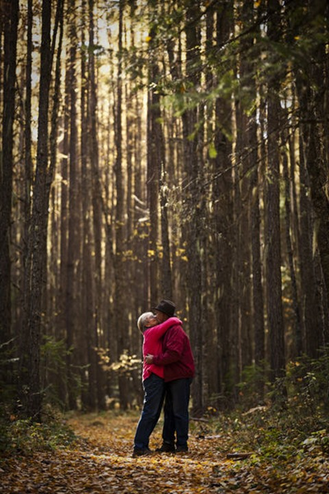 A happy retired couple laughing and smiling while on a hike through a forest during the fall in Sandpoint, Idaho.