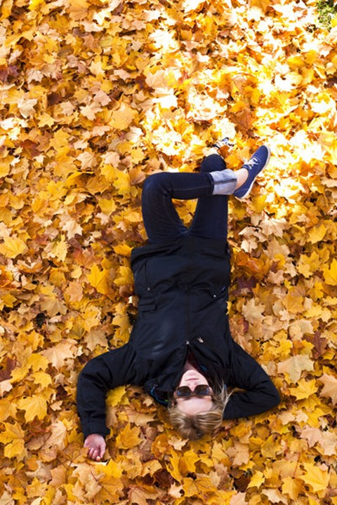 A beautiful young woman relaxing on a huge pile of orange leaves in the fall near Bozeman, Montana.