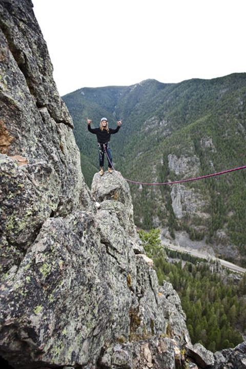 A young man rock climbing holds his hands in the air after climbing up a tower in Gallatin Canyon near Bozeman, Montana.
