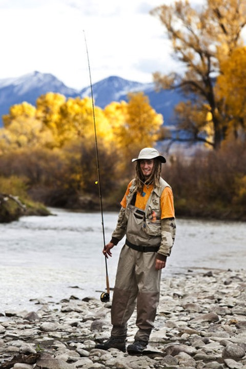 A athletic man fly fishing stands on the banks of the Yellowstone River with the fall colors and snowy mountains behind him in Bozeman, Montana.