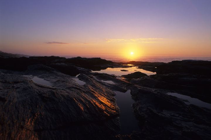 Sunrise over the Atlantic Ocean reflects in tidal pools at Two Lights State Park near Portland, ME