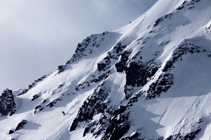 A athletic man skiing down a large exposed mountain on a sunny winter day in Cooke City, Montana.