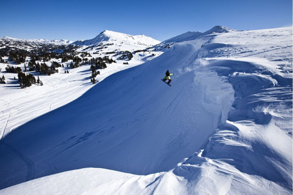 A snowboarder jumping off a cornice on a sunny winter day in Cooke City, Montana.