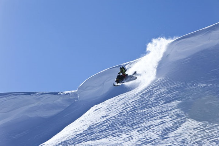 A snowmobiler jumping off a cornice on a sunny winter day in Cooke City, Montana.