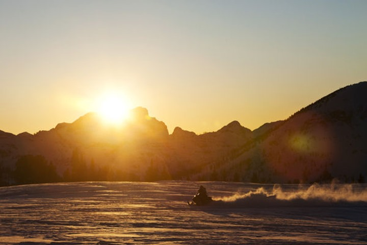 A athletic young man snowmobiling at sunset in Cooke City, Montana.