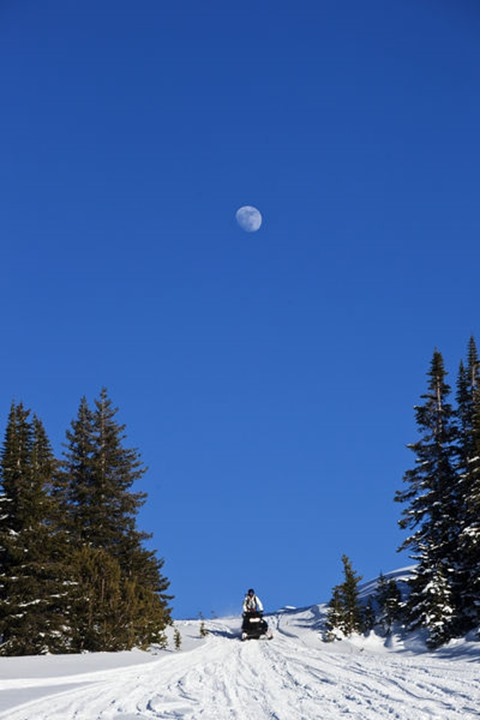 A athletic young man snowmobiling under the moon in Cooke City, Montana.