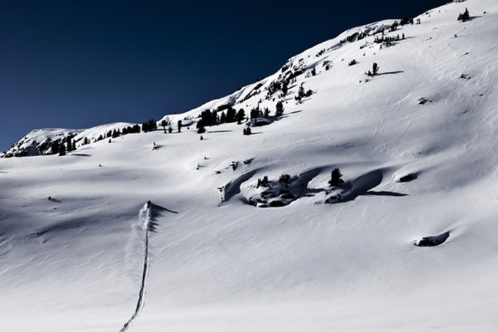 A athletic young man snowmobiling high marks on a untracked mountain in Cooke City, Montana.