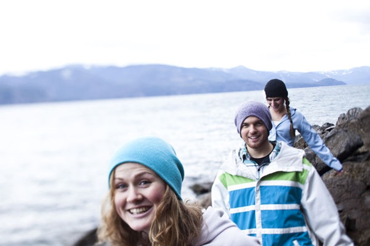 A group of three young adults smile while hiking at the edge of Lake Pend Oreille in Sandpoint, Idaho.