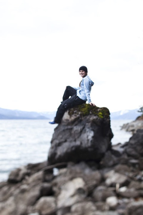 A young woman smiles while sitting on a rock next to a lake in Sandpoint, Idaho.