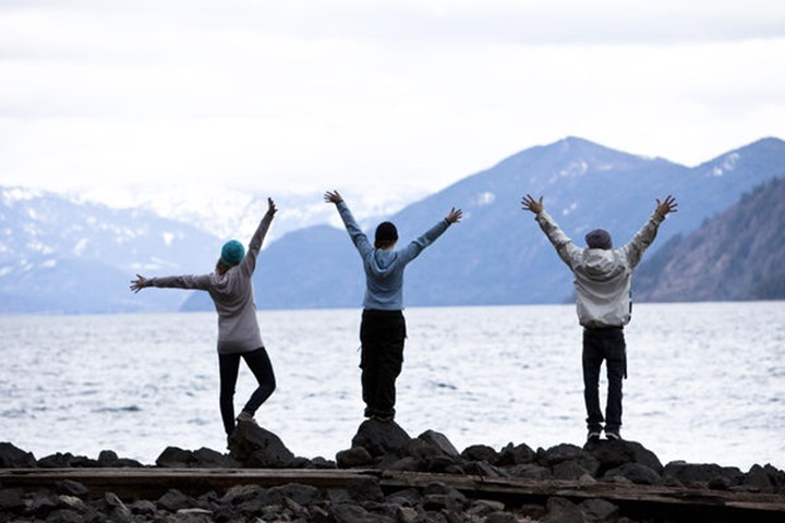 A group of three young adults standing with their arms open at the edge of Lake Pend Oreille in Sandpoint, Idaho.