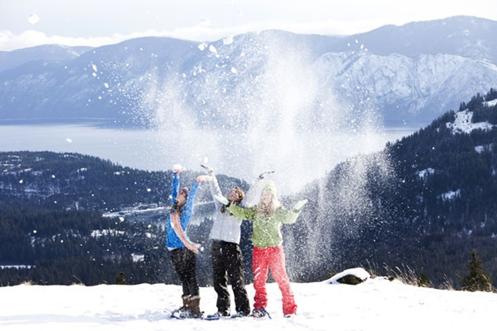 Three athletic young women throw snow in the air while snowshoeing on a beautiful day in Sanpoint, Idaho.