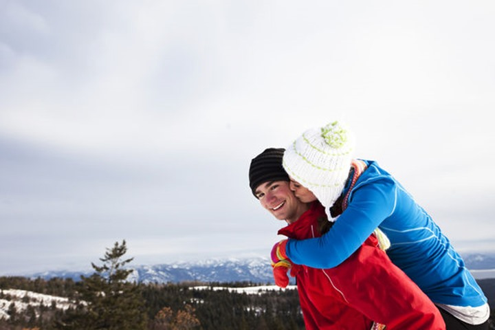 A young adult couple smile and kiss while snowshoeing on a winter day in Sandpoint, Idaho.
