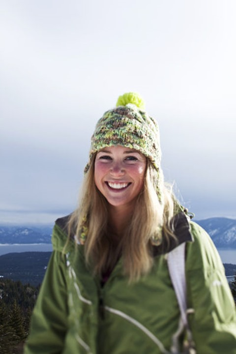 A beautiful young woman smiling stops for a portrait on a winter hike in Sandpoint, Idaho.