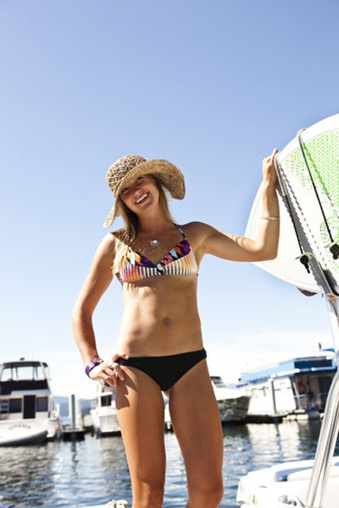 A athletic young woman smiles while standing next to a wakeboard boat in Sandpoint, Idaho.