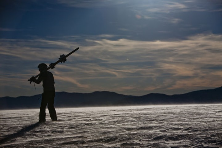 A silhouetted man stands holding his skis over his shoulder on the snow covered area of Max Patch, NC.