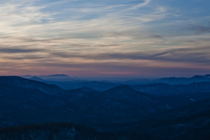 The sun sets over the Appalachian Mountain range seen from the summit of Max Patch, NC.