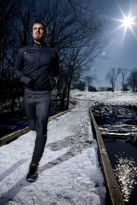 Carl Bakanowski runs on a bridge over a creek with snow on the ground in Seneca Park, Louisville, KY.