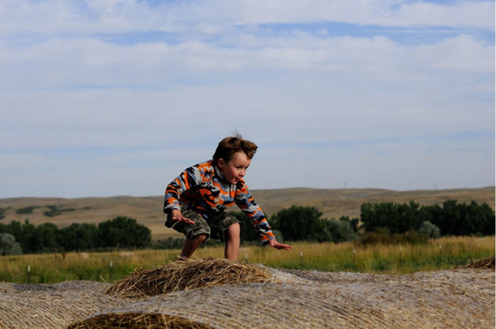 Young child enjoys playing outdoors in the summer in MT
