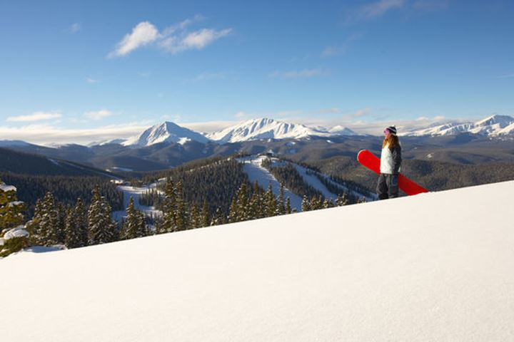 A snowboarder stands atop a cornice over looking a ski area.