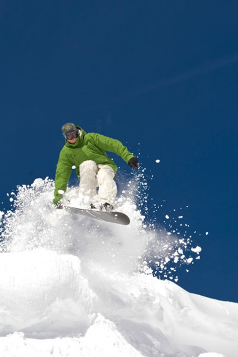 A snowboarder flies off of a snow-covered cornice.