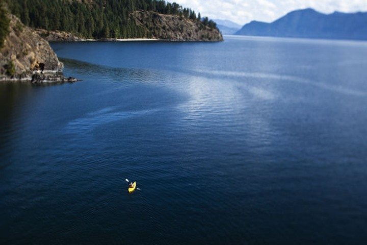 A athletic woman kayaking on Lake Pend Oreille in Sandpoint, Idaho.