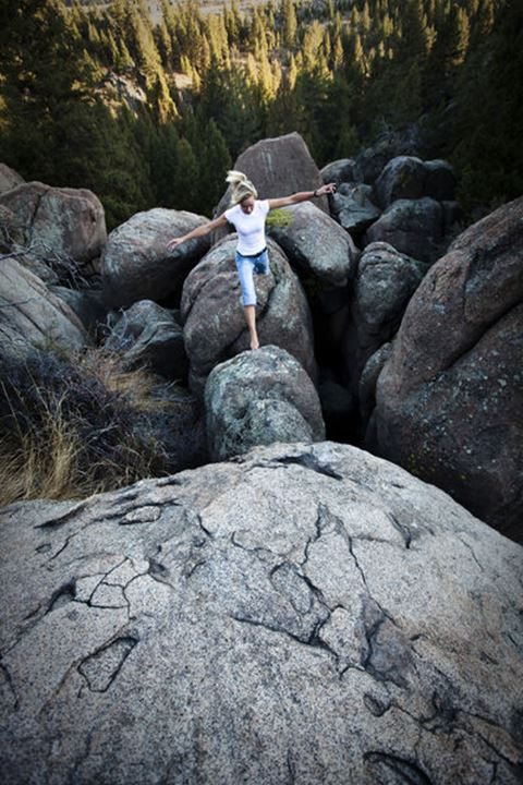 A athletic young woman leaping across a boulder field in Butte, Montana.