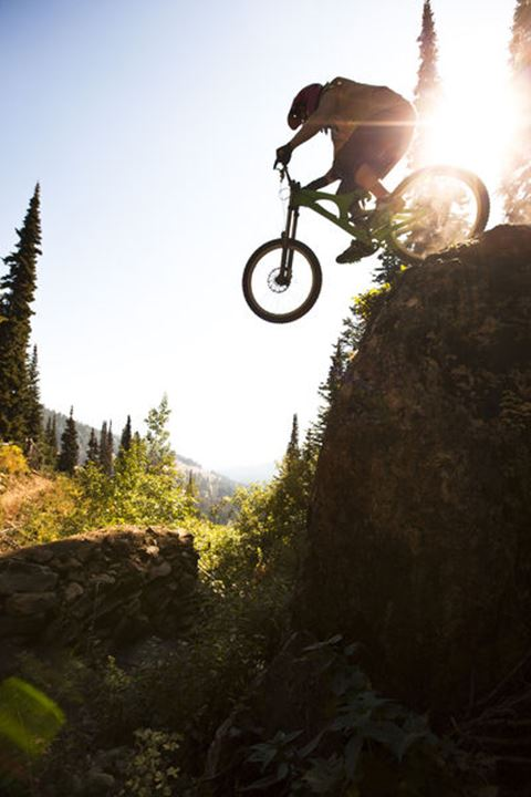 A athletic man mountain biking jumps off a large cliff while downhilling on Teton Pass in Jackson, Wyoming.