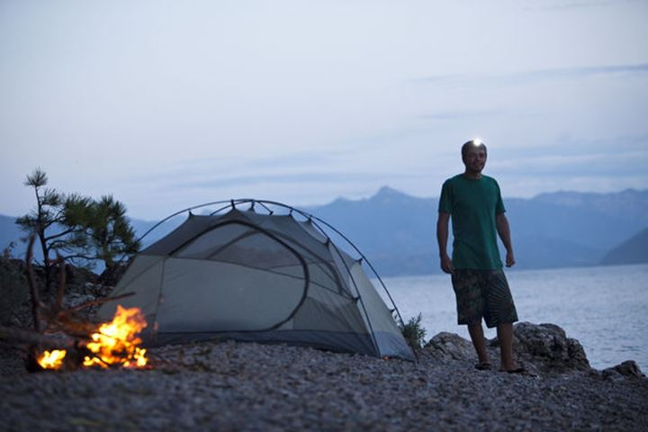 A young man smiling next to a campfire and tent on a camping trip with a head light on in Sandpoint, Idaho.