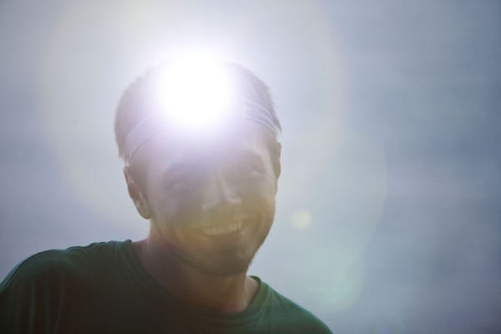 A young man smiling on a camping trip with a head light on in Sandpoint, Idaho.