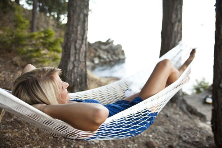 A beautiful young women smiling while sitting in a hammock next to a lake in Sandpoint, Idaho.