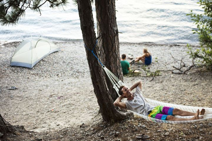 A group of young adults camping laugh and smile next to Lake Pend Oreille in Sandpoint, Idaho.