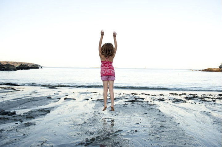 a girl jumps on the beach at fort williams, cape elizabeth, me.