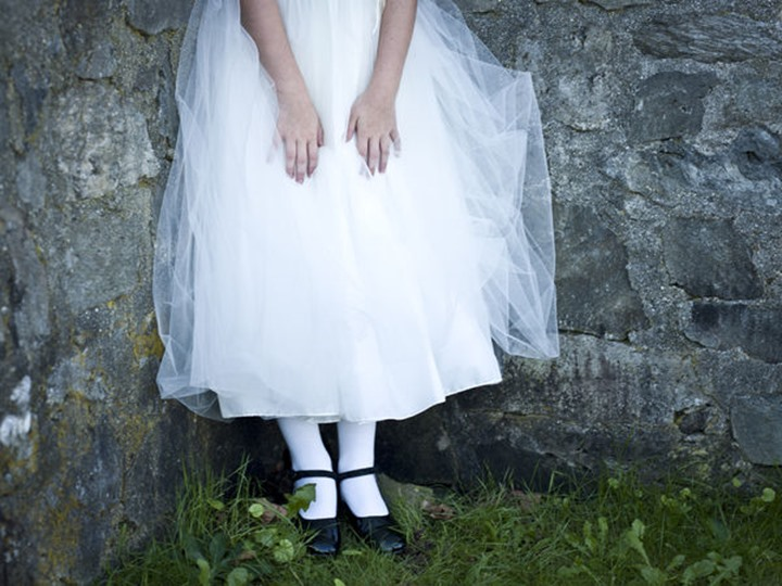 girl in a white dress leans against a stone wall