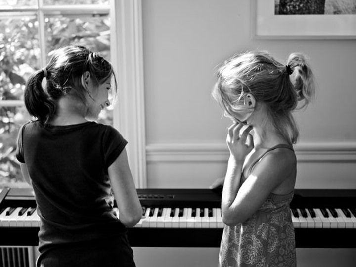 two friends practice the paino