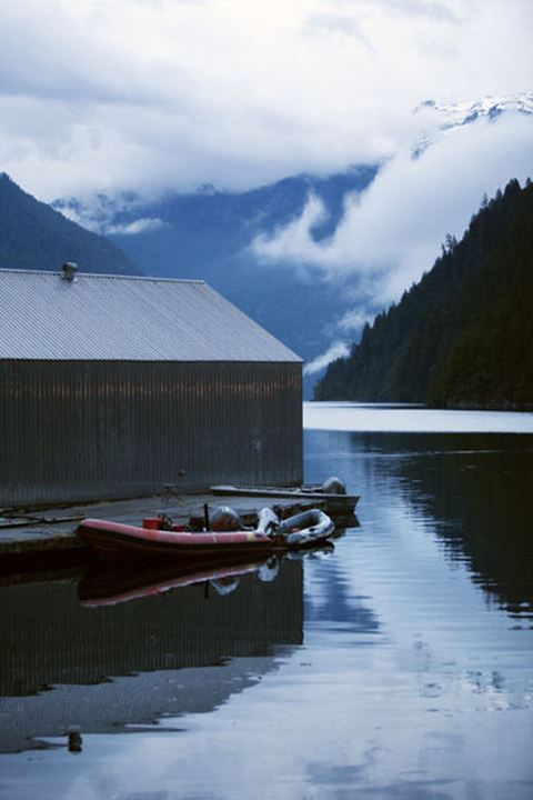 View of boats and a boathouse on an inlet in the coast range of British Columbia.