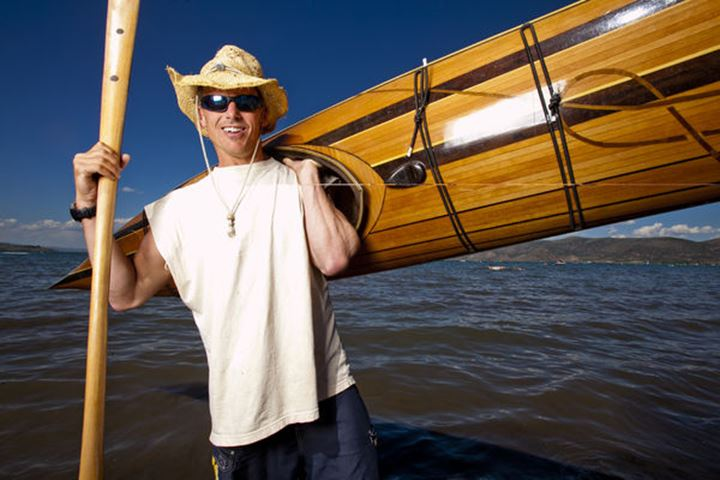 Thomas Glass wears a straw hat as he poses for a portrait with a wooden kayak and paddle that he made while standing on the shore of Bear Lake, Utah.