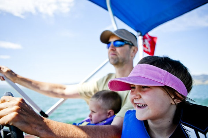 Brian Priebe pilots a pontoon boat while his three year old son John Priebe helps steer, and his five year old daughter sits next to them, Bear Lake, Utah.